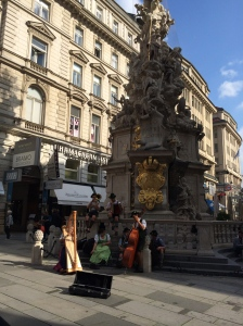 Street performers at the Plague Monument along the Graben
